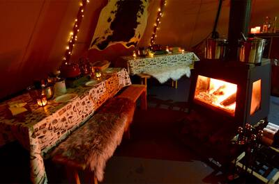 Inside of a tipi tent with dinner setting and fireplace