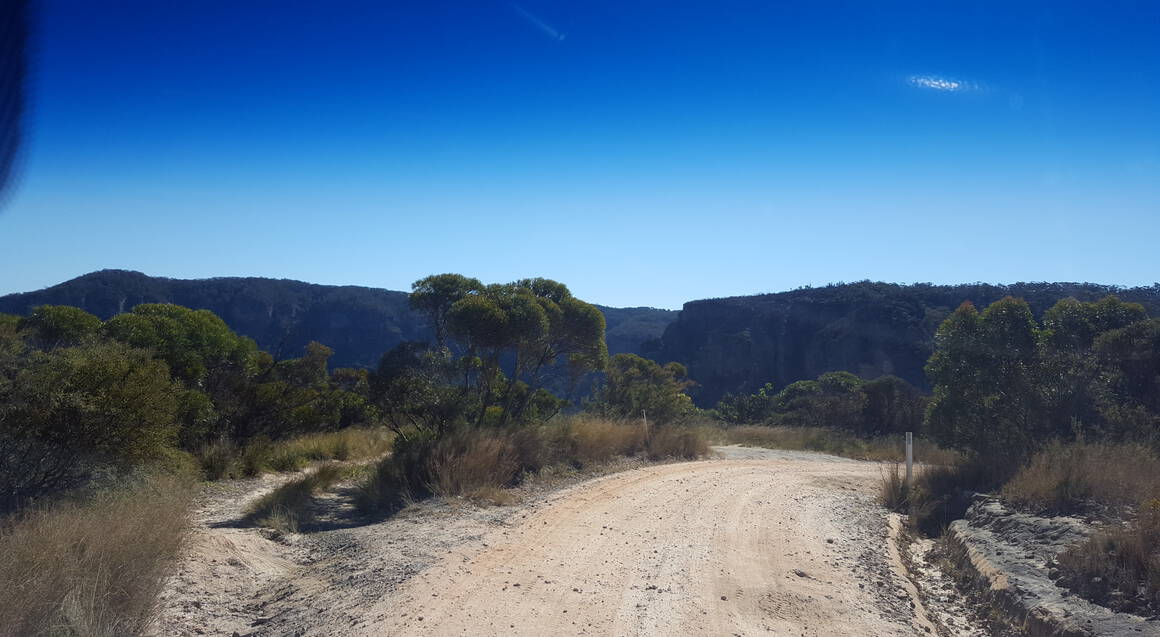 Mountain bike tour dirt track bushland and blue sky