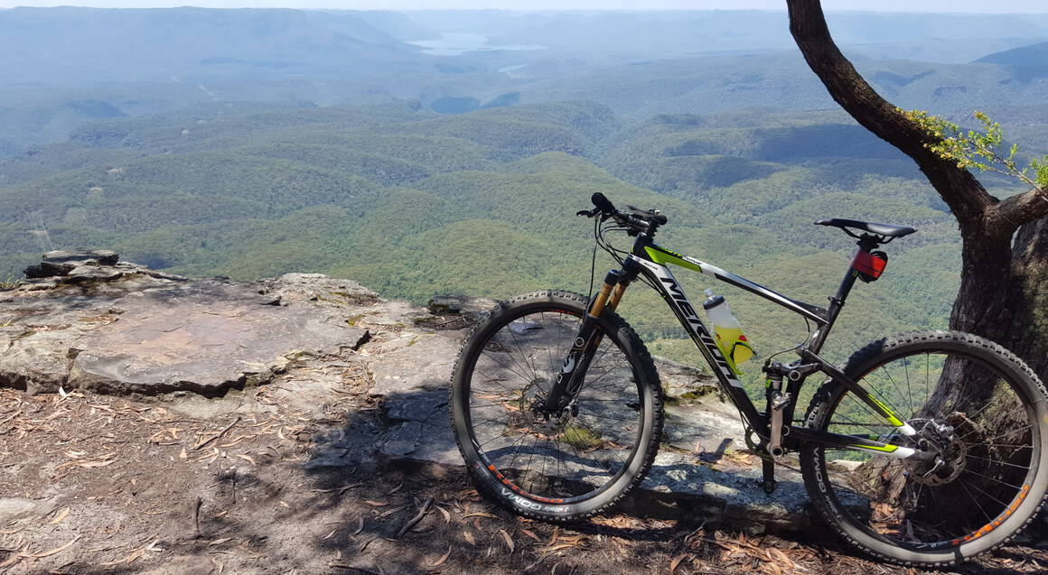 Mountain bike tour mountain bike parked on lookout a valley of green bushland and blue sky are the background