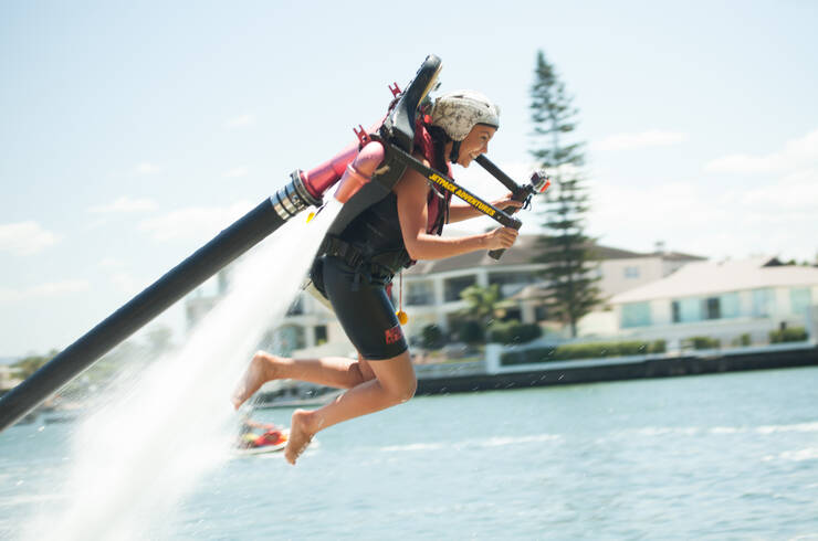 Woman flying over the water with a jet pack