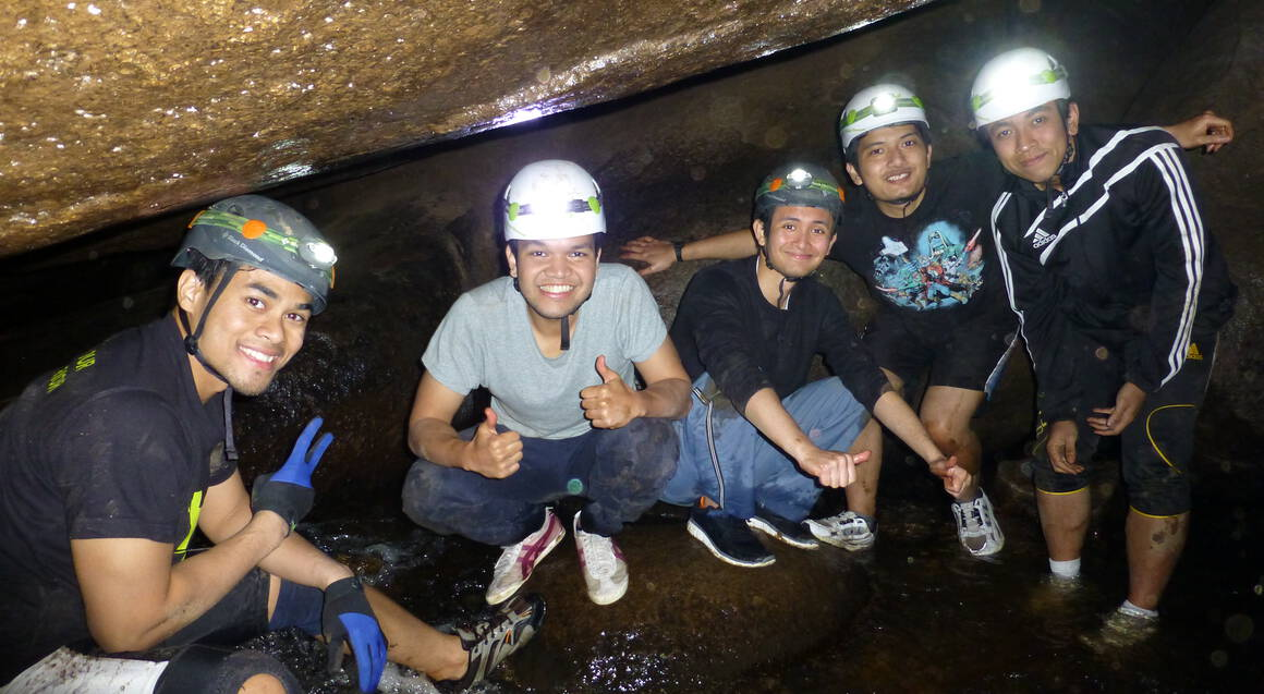 group inside a cave posing for a photo