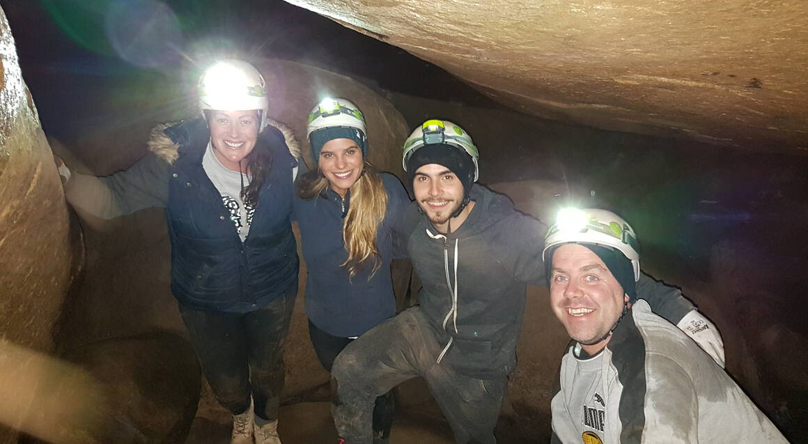 group of four people posing for a photo inside a cave at night
