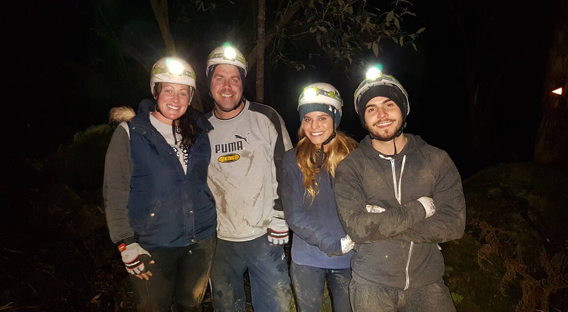 four people smiling for a photo wearing helmets and headlamps