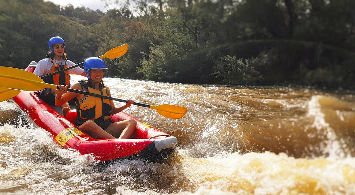 two people paddling down yarra river in a white water raft