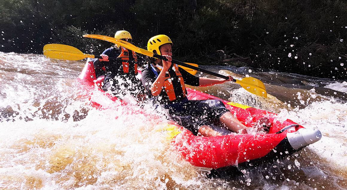two people paddling in a raft down yarra river white water rapids