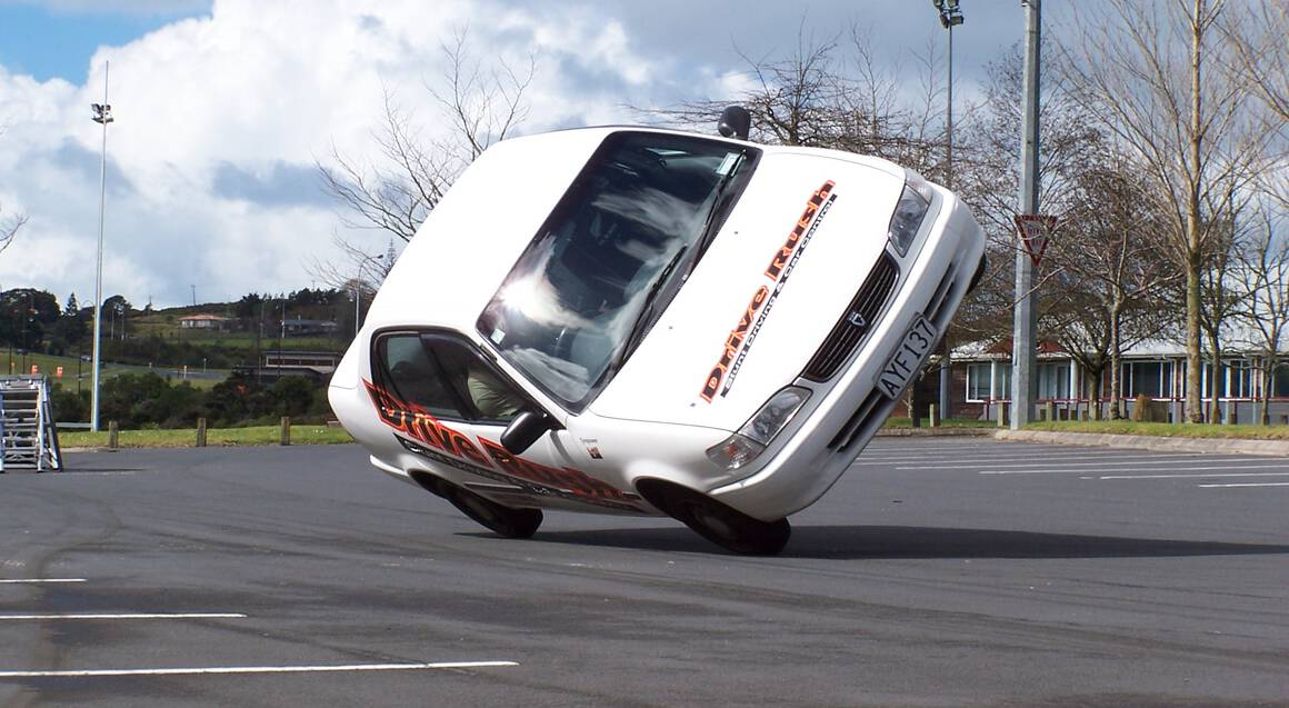 white car skidding on two right wheels